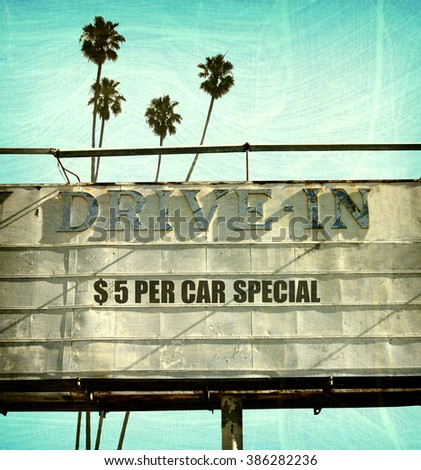 aged and worn vintage photo of retro drive in sign with palm trees