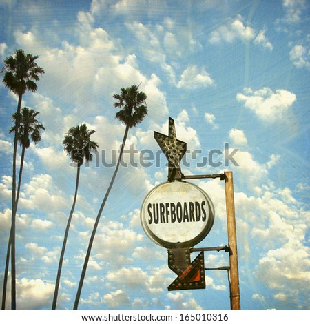 aged and worn vintage photo of surfboards sign and palm trees - stock photo