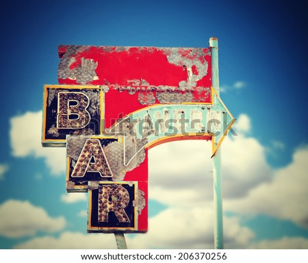 aged and worn vintage sign for a bar or tavern toned with a retro vintage instagram filter  - stock photo