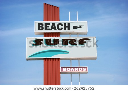 aged and worn vintage surf sign on beach - stock photo