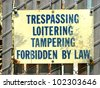 aged and worn vintage trespassing and loitering sign - stock photo