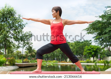 Aged Asian woman practicing warrior yoga pose outdoors - stock photo