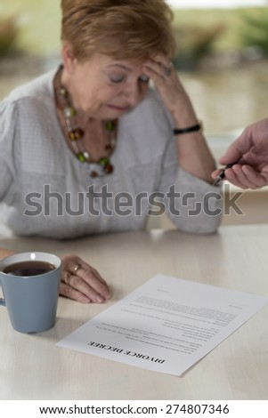 Aged broken down wife crying on divorce decree - stock photo