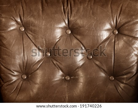 aged brown genuine leather upholstery of a chester sofa - stock photo