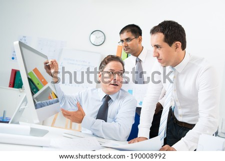 Aged businessman explaining idea to his colleagues while pointing at the monitor - stock photo