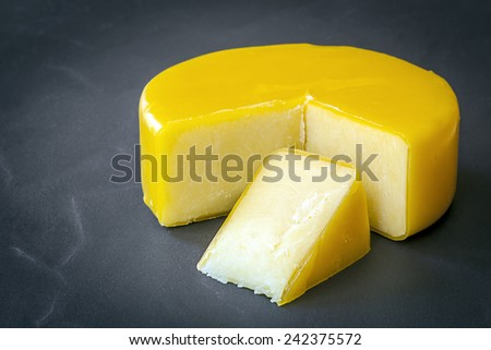 Aged cheddar cheese wheel on black slate. - stock photo