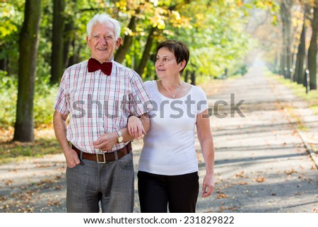 Aged cheerful marriage and autumn stroll in park - stock photo