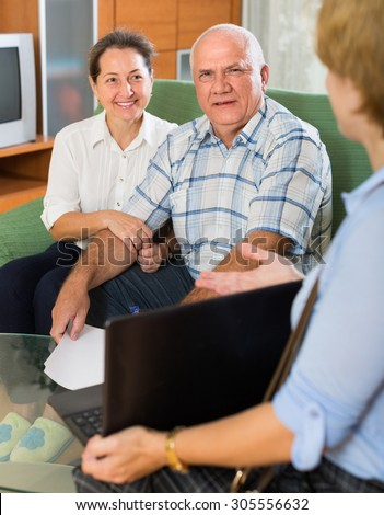 Aged couple answer questions of social worker with laptop at home and smiling. Focus on man