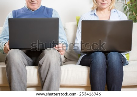 Aged couple sitting together with theirs computers - stock photo