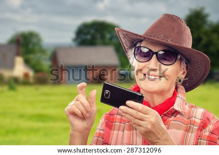 Aged cowgirl in red neckerchief has just made photos with smart phone. Now she looks them with pleasure. Old woman is wearing brown cowboy hat, red plaid shirt and sunglasses - stock photo