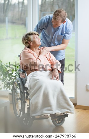 Aged disabled woman on wheelchair and her thoughtful male nurse - stock photo