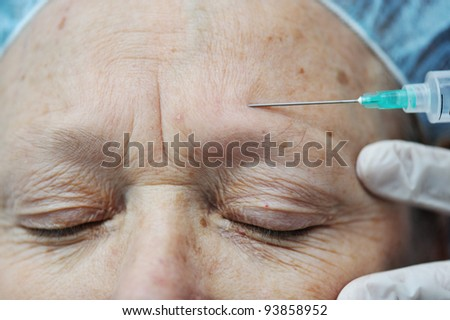 Aged female receiving injection in forehead - stock photo