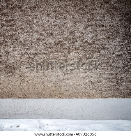 Aged gray plaster street wall and ground covered with snow