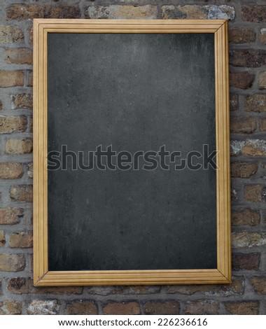 Aged green menu blackboard hanging on brick wall - stock photo