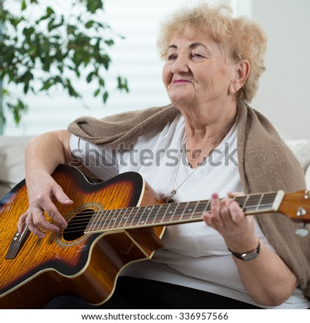 Aged happy woman playing the guitar in her room - stock photo