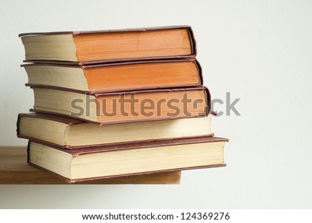 aged hardcover books stack on bookshelf