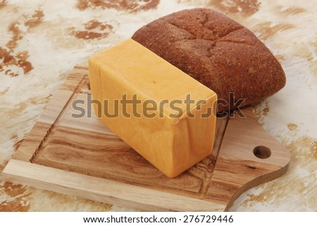 aged italian cheddar cheese on wooden board with rye ciabatta on used baking paper as background - stock photo