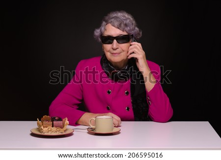 Aged lady in purple jacket calling by mobile phone while drinking coffee