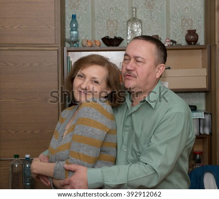 Aged man in shirt of grey-green color is embracing his smiling girlfriend closing his eyes.