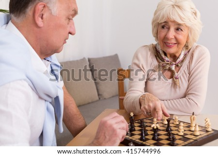 Aged married couple having fun on evening playing chess together