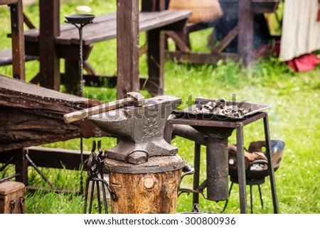 Aged medieval anvil and blacksmith tools - stock photo