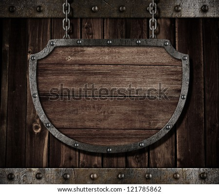 aged medieval shield signboard hanging on chains - stock photo