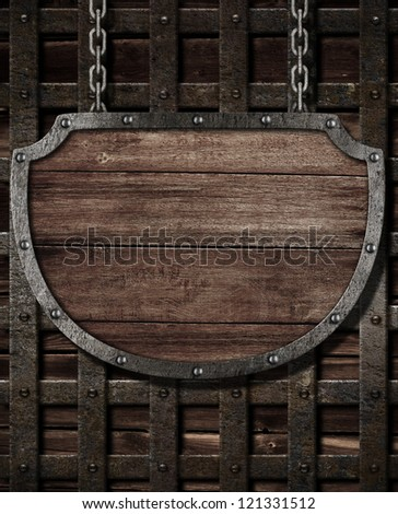 aged medieval shield signboard hanging on wooden gates - stock photo