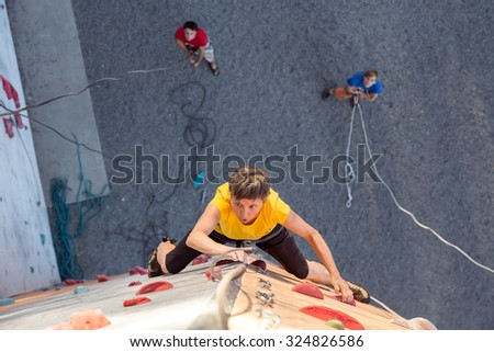 Aged Person Practicing Extreme Sport Elderly Female Climber Makes Hard Move on Outdoor Climbing Wall Sport Competitions High Up above Ground Belaying People on Remote Background - stock photo
