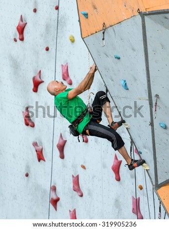 Aged Person Practicing Extreme Sport Elderly Male Climber Makes Hard Move and Looking High Up on Outdoor Climbing Wall Sport Competitions - stock photo