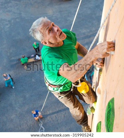 Aged Person Practicing Extreme Sport Elderly Male Climber Makes Hard Move Looking High Up on Outdoor Climbing Wall Sport Competitions Very Emotional Face Belaying Partner Fans Staying on Remote Ground - stock photo