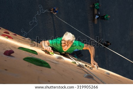 Aged Person Practicing Extreme Sport Elderly Male Climber Makes Hard Move on Outdoor Climbing Wall Sport Competitions Very Emotional Face Highlighted with Spotlight of Illumination - stock photo