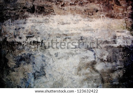 Aged, super-grunge concrete wall in dark, cold color tones. Gloomy, moody feel. Uneven, textured surface. Faded area in the center as copy space. - stock photo