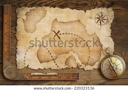 aged treasure map, ruler and old bronze compass on wooden table top view - stock photo