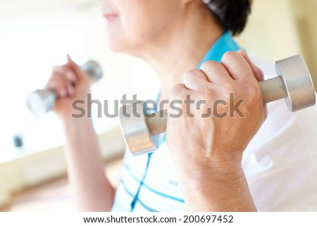 Aged woman doing physical exercise with barbells