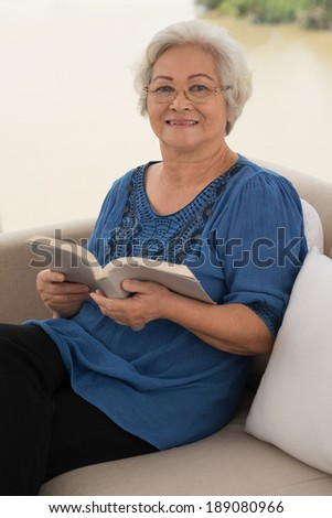 Aged woman reading a book while sitting on sofa - stock photo