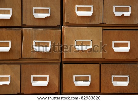 Aged wooden cabinet with square drawers and white handles. - stock photo