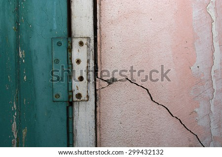 Aged wooden door with rusty hinges and shows structural damage wall crack - stock photo