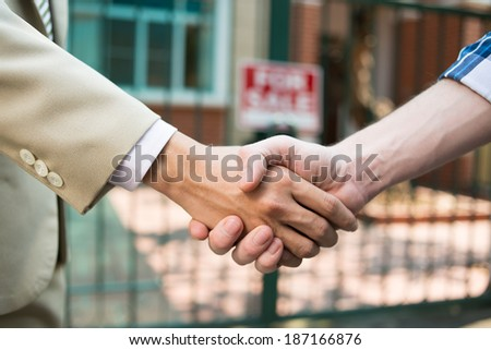 Agent and customer shaking hands - stock photo