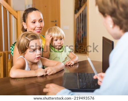 Agent consulting happy mother with two kids how to obtain insurance - stock photo
