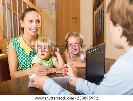Agent consulting smiling mother with two little children about insurance - stock photo