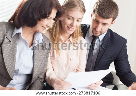 Agent. Financial consultant presents bank investments to a young couple - stock photo