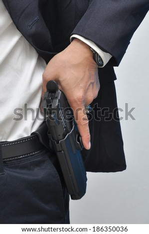 Agent wearing white shirt drawing gun from holster.
