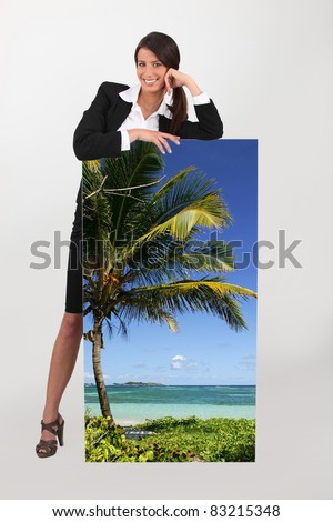 Agent with a poster of a tropical beach - stock photo