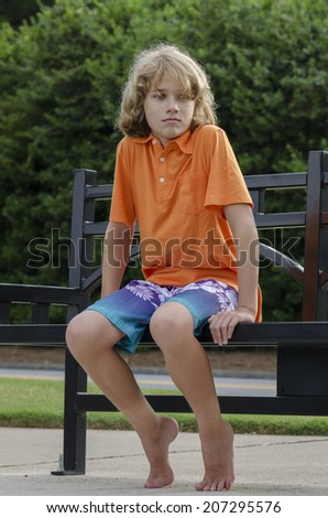 aggravated young man is seated on a bench thinking about stuff - stock photo
