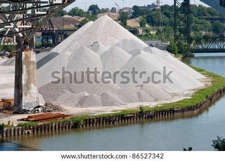 Aggregate Material:  Various aggregate materials used in the concrete making process are piled together on the bank of the Cuyahoga River in the flats industrial district of Cleveland, Ohio - stock photo