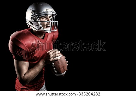 Aggressive American football player holding ball against black