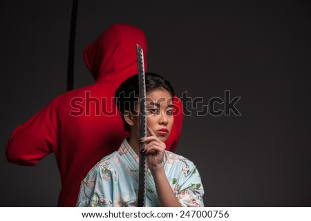 Aggressive beauty. Young beautiful Japanese woman in kimono looking at camera and holding katana sword by her face while standing back to back with warrior in red over grey background - stock photo