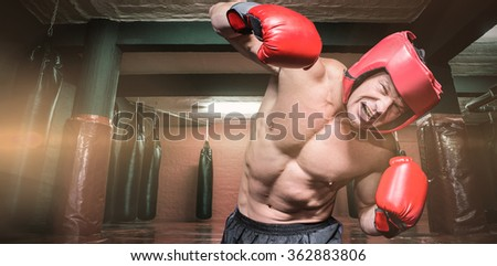 Aggressive boxer against black background against red boxing area with punching bags - stock photo