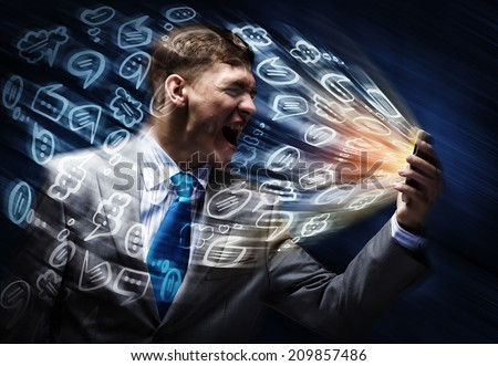 Aggressive businessman screaming fiercely in mobile phone - stock photo