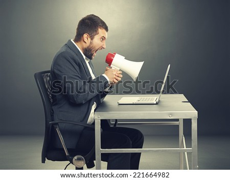 aggressive businessman screaming with megaphone and looking at laptop. photo in the dark room - stock photo